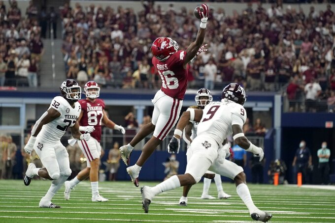 Arkansas wide receiver Treylon Burks (16) makes a one-handed catch between Texas A&M linebacker Andre White Jr. (32) and defensive back Leon O'Neal Jr. (9) in the first half of an NCAA college football game in Arlington, Texas, Saturday, Sept. 25, 2021. (AP Photo/Tony Gutierrez)