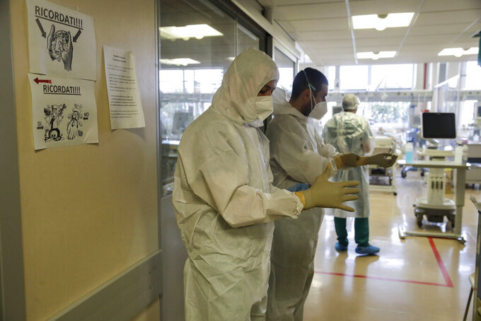 Nurses Simone and his colleague Luciano Ferreri wear their gloves as they prepare to enter the Intensive Care Unit at Varese's Circolo Hospital, in Varese, Italy, Friday, Nov. 6, 2020. During Italy's autumn pandemic resurgence, concern is falling less on intensive care wards and more on regular medical wards, as eight regions have seen the needle move alarmingly into the red-alert zone with more than half of hospital beds dedicated to coronavirus patients. (AP Photo/Luca Bruno)