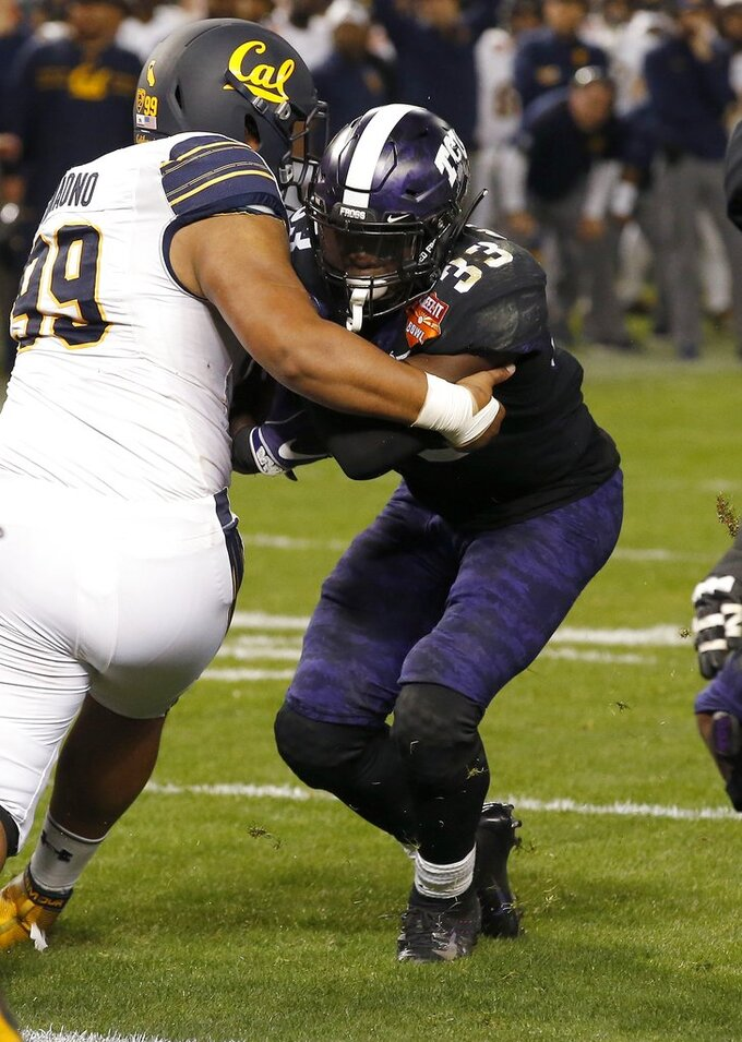 TCU running back Sewo Olonilua (33) heads to the end zone for a touchdown getting away from California nose tackle Siulagisipai Fuimaono (99) during the second half of the Cheez-It Bowl NCAA college football game Wednesday, Dec. 26, 2018, in Phoenix. TCU defeated California 10-7 in overtime. (AP Photo/Ross D. Franklin)