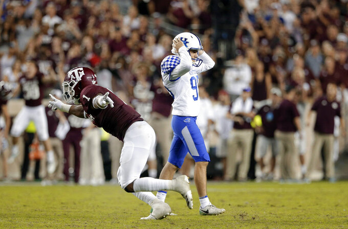 Texas A&M linebacker Buddy Johnson (1) runs off the field signaling no score as Kentucky place-kicker Miles Butler (95) reacts after missing a field goal in overtime during an NCAA college football game Saturday, Oct. 6, 2018, in College Station, Texas. (AP Photo/Michael Wyke)