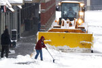 People clear snow in a shopping center after an overnight snowfall, Monday, Dec. 2, 2019, in Marlborough, Mass. (AP Photo/Bill Sikes)