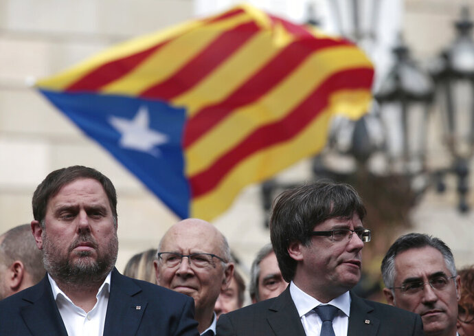 FILE - In this Monday, Oct. 2, 2017 file photo, Catalan regional Vice-President, Oriol Junqueras, left, and Catalan President, Carles Puigdemont, attend a protest called by pro-independence supporters outside the Palau Generalitat in Barcelona, Spain. Spain's Supreme Court is bracing to hold the nation's most sensitive trial in four decades of democracy this week with all eyes focused on its ability to stand up to concerted campaign by Catalonia's separatists to attack its credibility. Twelve high-profile Catalan separatists will face charges including rebellion for their role in a failed attempt to achieve secession for the prosperous north-eastern region in 2017. (AP Photo/Manu Fernandez, File)