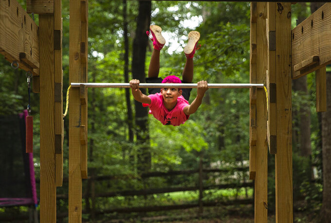 """Joey Ray, 12, uses apparatus in his family's Spotsylvania County, Va., backyard on Tuesday, Aug. 31, 2021.  Ray was selected to compete on the TV show """"American Ninja Warrior Junior."""" His episode will air Sept. 16 on Peacock. (Peter Cihelka/The Free Lance-Star via AP)"""