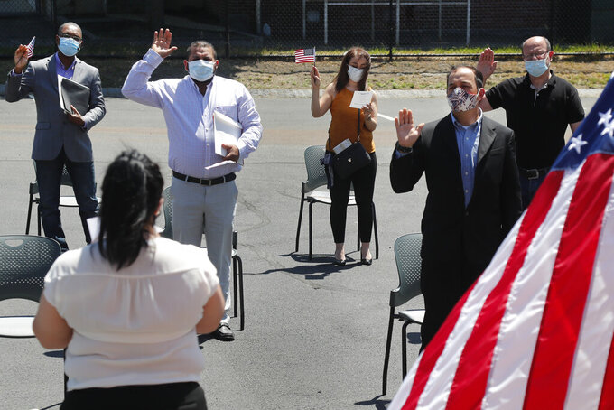 New citizens, socially distanced, are sworn in outside the U.S. Citizenship and Immigration Services building, Thursday, June 4, 2020, in Lawrence, Mass. The federal agency is resuming services in many cities across the country after being shuttered for more than two months because of the coronavirus pandemic. (AP Photo/Elise Amendola)