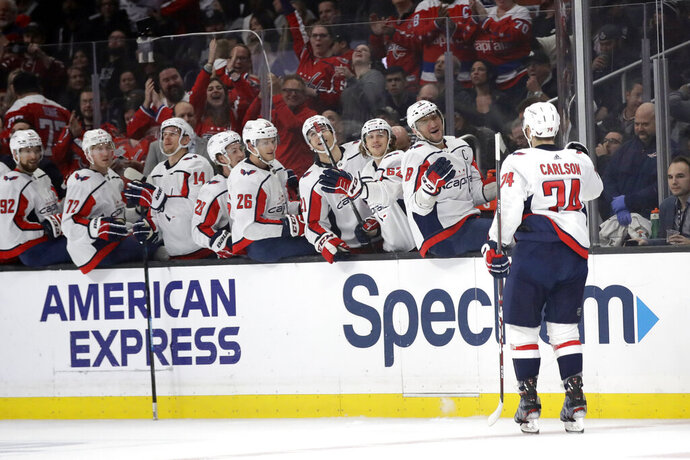 Washington Capitals' John Carlson (74) celebrates his goal with teammates on the bench during the first period of an NHL hockey game against the Los Angeles Kings Wednesday, Dec. 4, 2019, in Los Angeles. (AP Photo/Marcio Jose Sanchez)