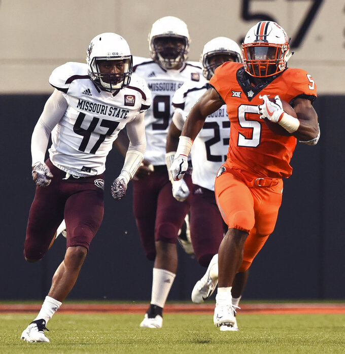 Oklahoma state running back Justice Hill (5) is chased by Missouri State safety Kam Carter (47), defensive tackle Kylin Washington (99), and linebacker Jordan Wilkes (23) during the first quarter of an NCAA college football game in Stillwater, Okla., Thursday, Aug. 30, 2018. (AP Photo/Brody Schmidt)