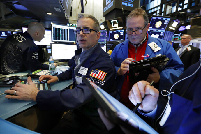 FILE- In this Feb. 5, 2019, file photo specialist Anthony Rinaldi, left, and trader Michael Conlon work on the floor of the New York Stock Exchange. The U.S. stock market opens at 9:30 a.m. EST on Wednesday, Feb. 13. (AP Photo/Richard Drew, File)