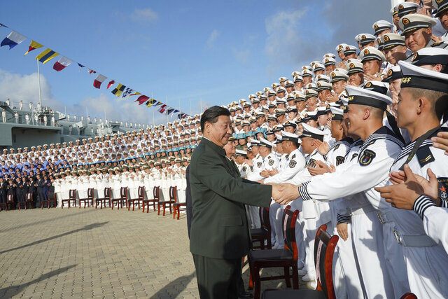 In this photo provided by China's Xinhua News Agency,  Chinese President Xi Jinping, center, meets with representatives of the aircraft carrier unit and the manufacturer at a naval port in Sanya, south China's Hainan Province, Tuesday, Dec. 17, 2019. President Xi attended the commissioning of China's first entirely home-built aircraft carrier, underscoring the country's rise as a regional naval power at a time of tensions with the U.S. and others over trade, Taiwan and the South China Sea.(Li Gang/Xinhua News Agency via AP)