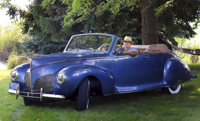 In this July 30, 2021, photo Dennis Moore, of Hamilton, Mont., sits in his 1940 Lincoln Zephyr that was used by the Glacier Transportation Company in the 1940s to transport dignitaries through the scenic Glacier National Park. Moore bought the car at an estate auction in Oct. 2018, restored it and it drove it this week to California for a classic car show in Pebble Beach. (Perry Backus/Ravalli Republic via AP)