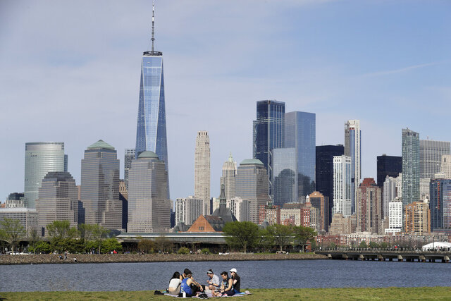 FILE - In this Saturday, May 2, 2020 file photo, people sit in view of Lower Manhattan at Liberty State Park in Jersey City, N.J. Rising cases of COVID-19 in the nation and Northeast may lead to New York, New Jersey and Connecticut re-thinking how they add other states to their quarantine list. Gov. Andrew Cuomo said he'll release an update Wednesday to his plan that designates parts of New York City and suburban communities as hot spots where schools and nonessential businesses are closed. (AP Photo/Seth Wenig, File)