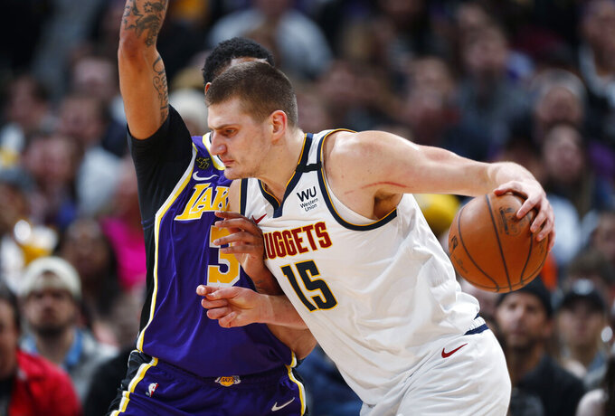 FILE - In this Feb. 12, 2020, file photo, Denver Nuggets center Nikola Jokic drives as Los Angeles Lakers forward Anthony Davis defends during the first half of an NBA basketball game in Denver. A person with knowledge of the situation says Jokic has tested positive for the coronavirus and is quarantining in his native Serbia. (AP Photo/David Zalubowski, File)