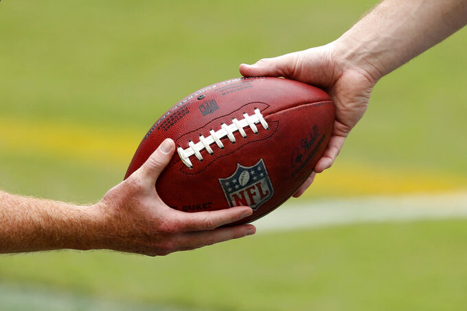 Philadelphia Eagles' Cameron Johnston, left, hands a football to Rick Lovato before an NFL football game against the Cincinnati Bengals, Sunday, Sept. 27, 2020, in Philadelphia. (AP Photo/Laurence Kesterson)