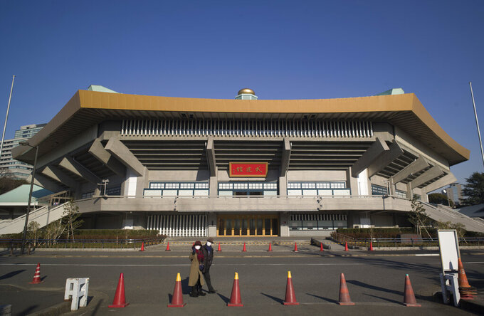 FILE - In this Thursday, Jan. 21, 2021, file photo, a man and a woman walk past the Nippon Budokan arena in Tokyo. Judo is coming home at the Tokyo Olympics, and the Japanese team is under a world of pressure. As if this eight-day tournament wasn't already significant enough, the players will compete at the Nippon Budokan, the hallowed arena built for the first Olympic judo events. (AP Photo/Hiro Komae, File)