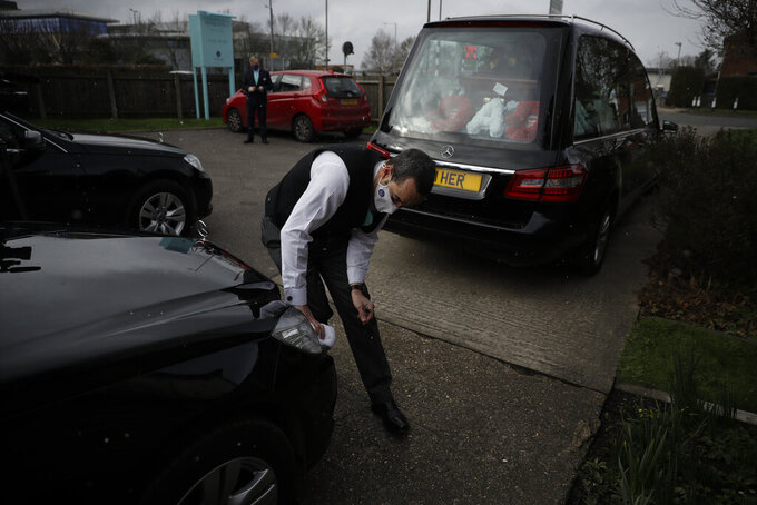 Senior Funeral Director Ben Blunt wipes down a limousine during a light snow fall outside Heritage & Sons Funeral Directors in Aylesbury, southern England, Wednesday, Feb. 10, 2021. Funeral home staff are under pressure in many places, but the burden is especially intense in Britain, where more than 115,000 people with the virus have died. (AP Photo/Matt Dunham)