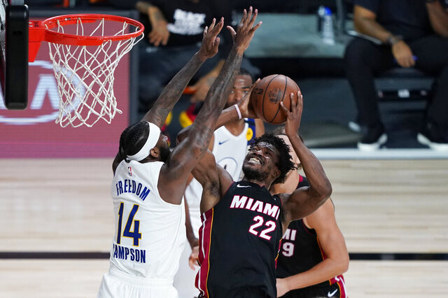 Miami Heat forward Jimmy Butler (22) drives to the basket against Indiana Pacers forward JaKarr Sampson (14) during the second half of an NBA basketball first round playoff game, Saturday, Aug. 22, 2020, in Lake Buena Vista, Fla. (AP Photo/Ashley Landis, Pool)