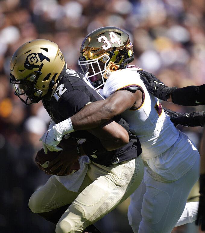 Minnesota defensive lineman Boye Mafe, right, sacks Colorado quarterback Brendon Lewis in the first half of an NCAA college football game Saturday, Sept. 18, 2021, in Boulder, Colo. (AP Photo/David Zalubowski)