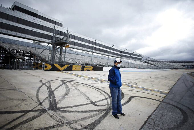 Mike Tatoian, president and CEO of Dover International Speedway, stands near the finish line while waiting for a news conference at the track, Monday, April 27, 2020, in Dover, Del. The track was scheduled to host a NASCAR auto race this weekend, but due to the COVID-19 outbreak, the race is bring run virtually on NASCAR's iRacing circuit. Sports will eventually start again and all signs indicate NASCAR is racing full speed ahead of the other major leagues in resuming competition. The sanctioning body is currently working on a revised schedule that could have NASCAR back on track in roughly three weeks.(AP Photo/Matt Slocum)