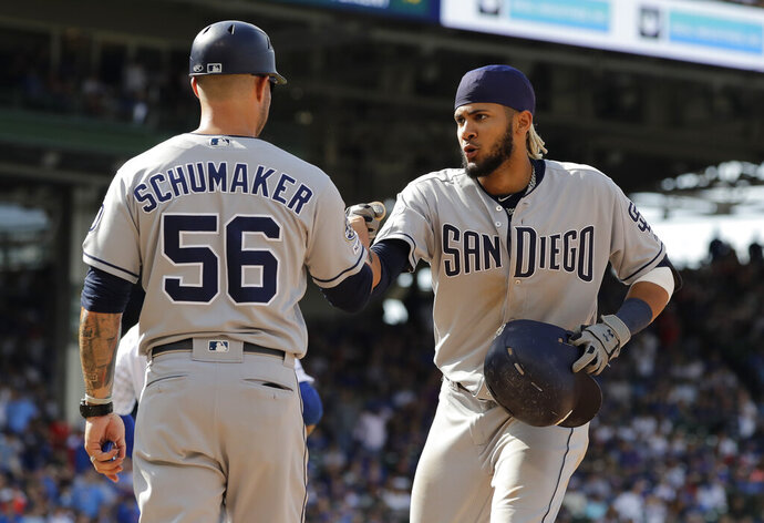 San Diego Padres' Fernando Tatis Jr., right, celebrates with first base coach Skip Schumaker after hitting a two-run single during the ninth inning of a baseball game against the Chicago Cubs in Chicago, Sunday, July 21, 2019. (AP Photo/Nam Y. Huh)