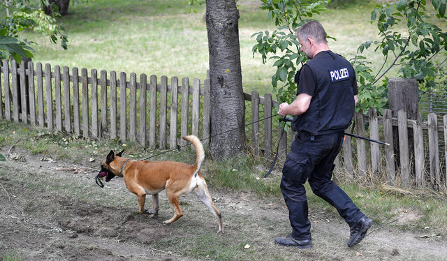 Germany police officers search with dogs an allotment garden plot in Seelze, near Hannover, Germany, Wednesday, July 29, 2020. Police have begun searching an allotment garden plot, believed to be in connection with the 2007 Portugal disappearance of missing British girl Madeleine McCann. (AP Photo/Martin Meissner)