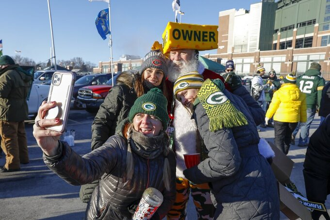 Fans take a selfie outside Lambeau Field before an NFL football game between the Green Bay Packers and the Chicago Bears Sunday, Dec. 15, 2019, in Green Bay, Wis. (AP Photo/Mike Roemer)