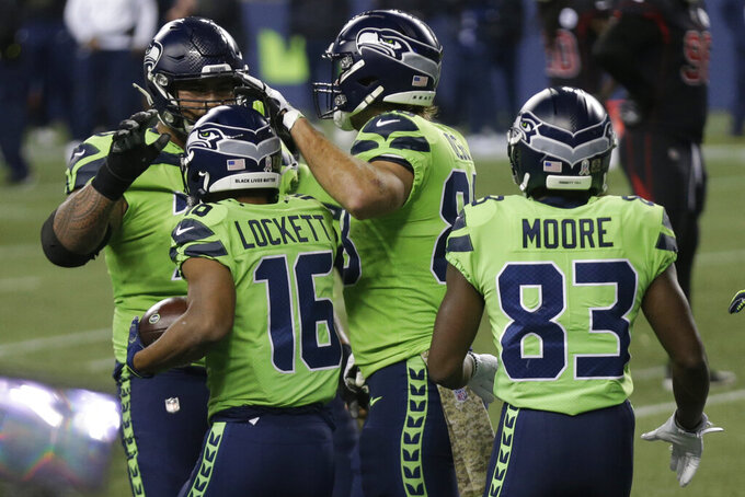 Seattle Seahawks wide receiver Tyler Lockett (16) is greeted by teammates after he caught a pass for a touchdown against the Arizona Cardinals during the first half of an NFL football game, Thursday, Nov. 19, 2020, in Seattle. (AP Photo/Lindsey Wasson)