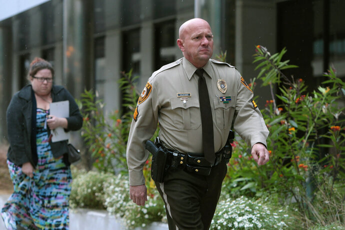 "FILE - In this Oct. 24, 2019 file photo, St. Louis County police Sgt. Keith Wildhaber returns from a lunch break to the St. Louis County courthouse on the third day of his discrimination case against the county in Clayton, Mo.  St. Louis County has agreed to a $10.25 million settlement with Wildhaber, a gay police lieutenant who says he was passed over for promotion 23 times and was told to ""tone down"" his ""gayness."