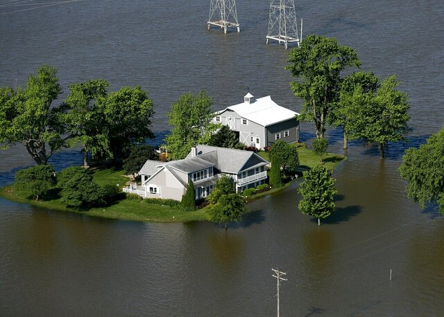 FILE - In this June 5, 2019, file photo, Mississippi River flood water surrounds a home built on high ground outside of West Alton, Mo. With flood concerns already high in the Midwest, the U.S. Army Corps of Engineers is warning that many levees on the Missouri and Kansas rivers that were damaged during last year's devastating floods remain vulnerable to high water. (David Carson/St. Louis Post-Dispatch via AP, File)