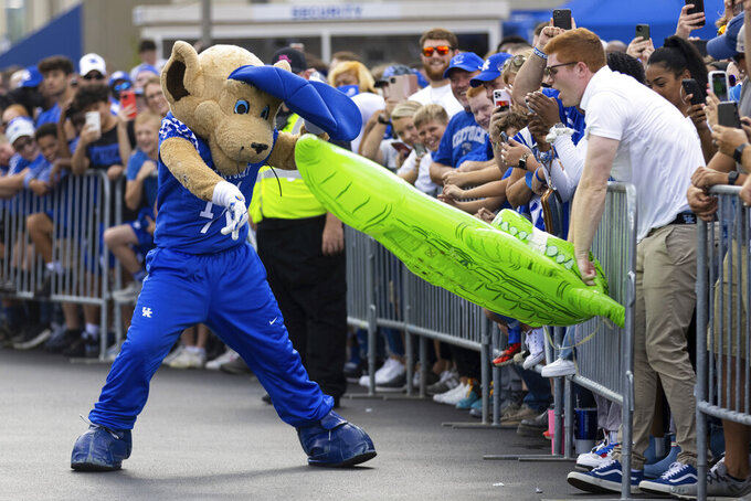 Kentucky's mascot, left, beats up an inflatable alligator with a fan before an NCAA college football game against Florida in Lexington, Ky., Saturday, Oct. 2, 2021. (AP Photo/Michael Clubb)