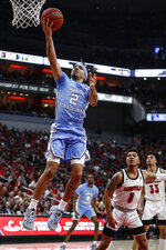 North Carolina guard Cole Anthony (2) shoots a layup in front of Louisville guard Lamarr Kimble (0) during an NCAA college basketball game Saturday, Feb. 22, 2020, in Louisville, Ky. (AP Photo/Wade Payne)