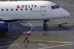 FILE - In this Feb. 5, 2019, file photo a ramp worker guides a Delta Air Lines plane at Seattle-Tacoma International Airport in Seattle. Delta Air Lines reports earns Tuesday, Oct. 8. (AP Photo/Ted S. Warren, File)