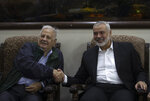 Palestinian Hamas movement chief, Ismail Haniyeh, right, shakes hands with the head of the Central Elections Commission, Hanna Nasser, during a meeting in Gaza City, Monday, Oct. 28, 2019. The militant Hamas group that runs the Gaza Strip says it's ready to go for Palestinian elections. (AP Photo/Khalil Hamra)