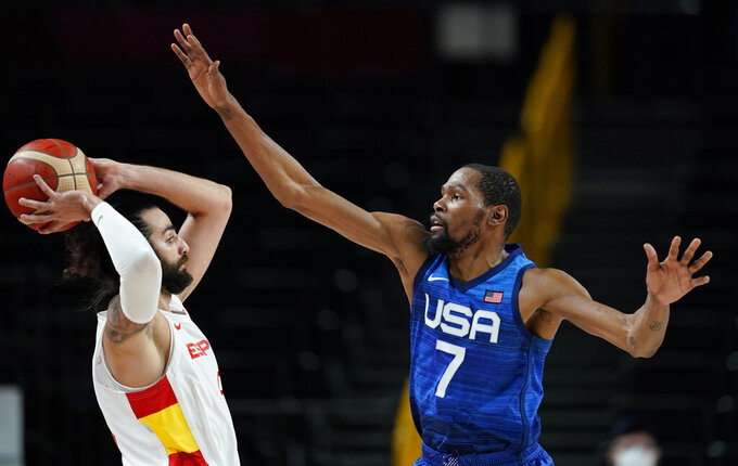 United States' Kevin Durant (7), right, tries to block Spain's Ricky Rubio (9), left, during men's basketball quarterfinal game at the 2020 Summer Olympics, Tuesday, Aug. 3, 2021, in Saitama, Japan. (AP Photo/Charlie Neibergall)