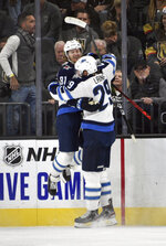 Winnipeg Jets left wing Kyle Connor (81) celebrates with right wing Patrik Laine after scoring in overtime against the Vegas Golden Knights during an NHL hockey game Saturday, Nov. 2, 2019, in Las Vegas. (AP Photo/David Becker)