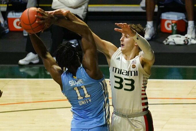 Miami forward Matt Cross (33) defends North Carolina forward Day'Ron Sharpe (11) during the second half of an NCAA college basketball game, Tuesday, Jan. 5, 2021, in Coral Gables, Fla. North Carolina defeated Miami 67-65. (AP Photo/Marta Lavandier)