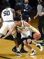 Vanderbilt guard Scotty Pippen Jr. (2) drives around teammate Ejike Obinna (50) and Auburn guard Sharife Cooper, second from left, during the second half of an NCAA college basketball game, Tuesday, Feb. 9, 2021, in Nashville, Tenn. Auburn won 73-67. (AP Photo/Mark Zaleski)