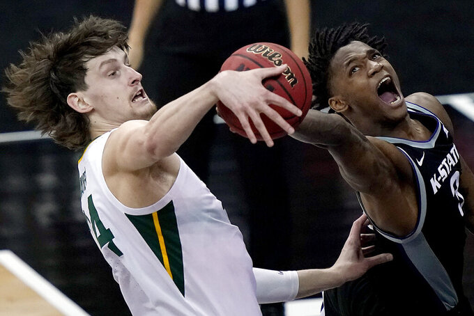 Baylor's Matthew Mayer, left, blocks a shot by Kansas State's DaJuan Gordon (3) during the first half of an NCAA college basketball game in the second round of the Big 12 Conference tournament in Kansas City, Mo., Thursday, March 11, 2021. (AP Photo/Charlie Riedel)