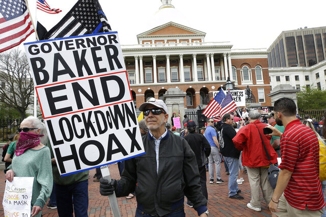 Demonstrators display flags and placards during a protest, Monday, May 4, 2020, in front of the Statehouse, in Boston. Protesters gathered in front of the Statehouse Monday to protest restrictions on movement and businesses prompted by the COVID-19 outbreak. (AP Photo/Steven Senne)