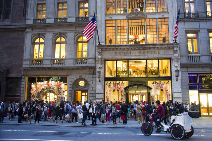 FILE- In this Sept. 8, 2011, file photo shoppers gather outside the Henri Bendel store on Fifth Avenue during Fashion's Night Out in New York. Henri Bendel, known for its brown and white striped shopping bags, is closing in the new year. The luxury retailer's parent company, L Brands Inc., said that Henri Bendel's 23 stores and its website will shut down in January but that it'll carry new merchandise during the holiday season. (AP Photo/Charles Sykes, File)
