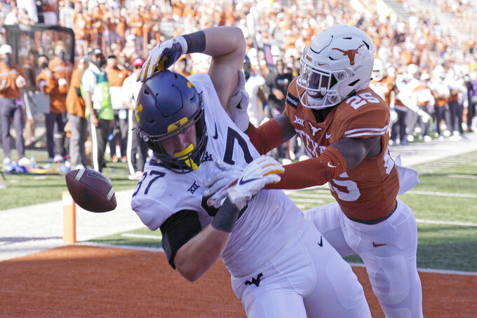 Texas' B.J. Foster (25) knocks the ball away from West Virginia's Mike O'Laughlin (87) during the second half of an NCAA college football game in Austin, Texas, Saturday, Nov. 7, 2020. (AP Photo/Chuck Burton)