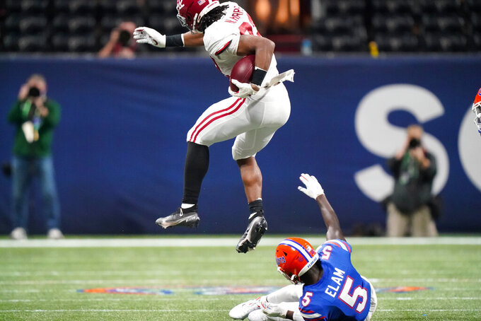 Alabama running back Najee Harris (22) leaps over Florida defensive back Kaiir Elam (5) during the second half of the Southeastern Conference championship NCAA college football game, Saturday, Dec. 19, 2020, in Atlanta. (AP Photo/Brynn Anderson)