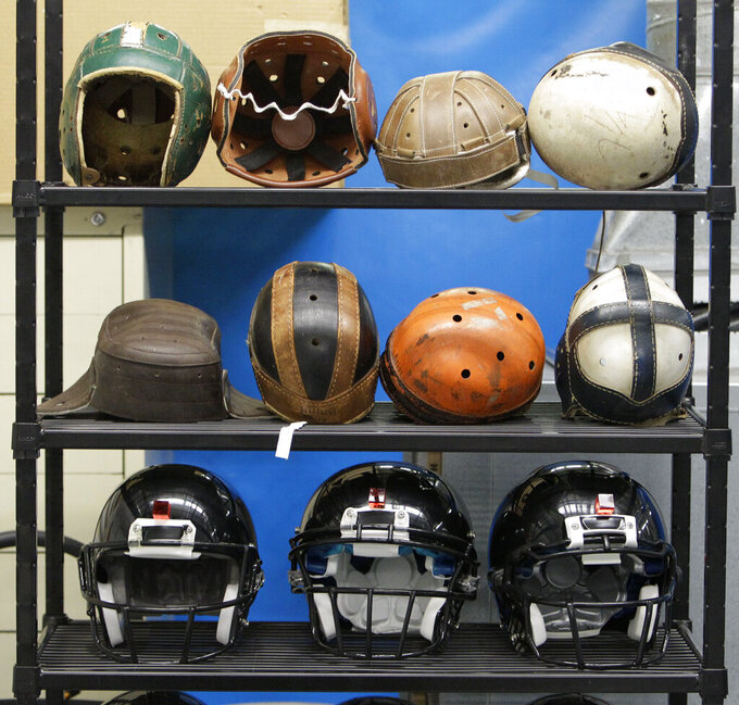 FILE - In this Sept. 23, 2010, file photo, various football helmets, used for testing helmet-to-helmet collisions, are displayed on a rack at a laboratory in the Cleveland Clinic's Lutheran Hospital in Cleveland. Helmets have evolved from the original hard leather of the NFL's infancy to hard polycarbonate single-piece shells with various amounts of padding and air bladders that served as the primary form of head protection into the beginning of this century.  (AP Photo/Mark Duncan, File)