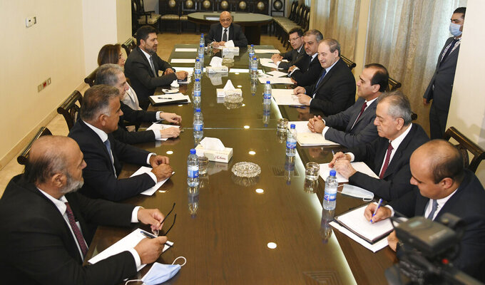In this photo released by the Syrian official news agency SANA, Syria's Foreign Minister Faisal Mekdad, third right, meets with Lebanese Energy Minister Raymond Ghajar, left, caretaker Defense Minister and acting Foreign Minister Zeina Akar, second left, Lebanon's Finance Minister Ghazi Wazni, third right, and Lebanon's top negotiator and security chief Abbas Ibrahim in Damascus, Syria, Saturday, Sept. 4, 2021. A senior Lebanese government delegation arrived in Syria on Saturday for talks expected to focus on the crippling fuel crisis that has paralyzed Lebanon. It marked the highest official visit since Syria's civil war began more than a decade ago. (SANA via AP)