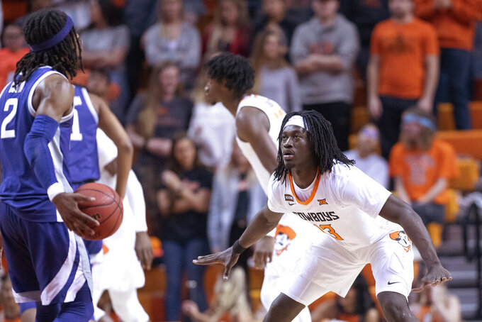 Oklahoma State guard Isaac Likekele (13) defends against Kansas State guard Cartier Diarra (2) during the first half of an NCAA college basketball game in Stillwater, Okla., Wednesday, March 4, 2020. (AP Photo/Brody Schmidt)