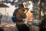 A firefighter gets caught off-guard by a flare up of the Palisades Fire in the Highlands neighborhood in the Pacific Palisades area of Los Angeles, Monday, Oct. 21, 2019. (AP Photo/Christian Monterrosa)