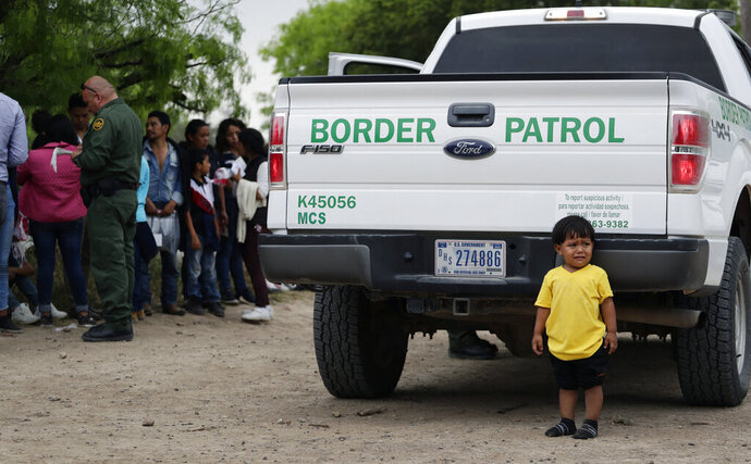In this Thursday, March 14, 2019, photo, William Josue Gonzales Garcia, 2, who was traveling with his parents, waits with other families who crossed the nearby U.S.-Mexico border near McAllen, Texas. They are waiting for Border Patrol agents to check names and documents. Immigration authorities say they expect the ongoing surge of Central American families crossing the border to multiply in the coming months. (AP Photo/Eric Gay)