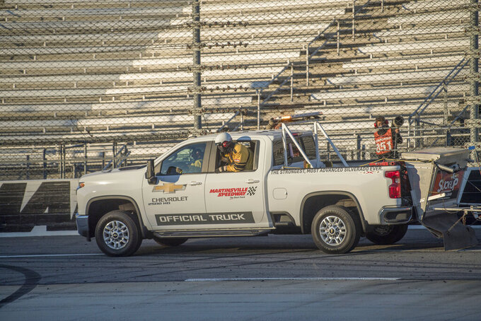 A track official looks for objects on the track after a spin-out during a NASCAR Xfinity Series auto race at the Martinsville Speedway in Martinsville, Va., Saturday, Oct.31, 2020. (AP Photo/Lee Luther Jr.)