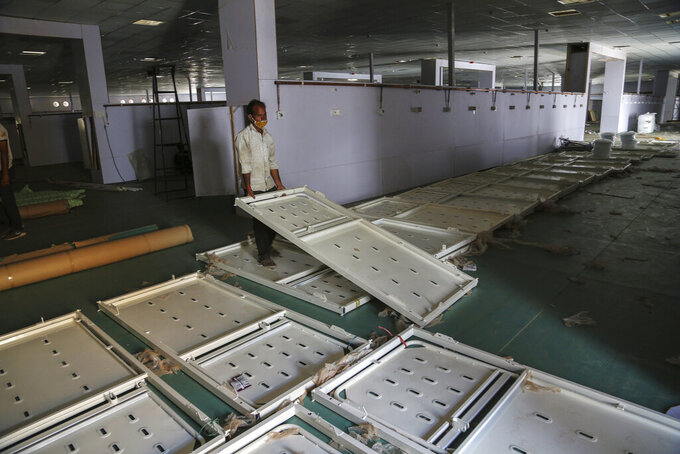 An Indian laborer works during the setting up of a temporary 500 bedded COVID-19 hospital by the Defence Research and Development Organization in Jammu, India, Monday, May 24, 2021. India crossed another grim milestone Monday of more than 300,000 people lost to the coronavirus as a devastating surge of infections appeared to be easing in big cities but was swamping the poorer countryside. (AP Photo/Channi Anand)