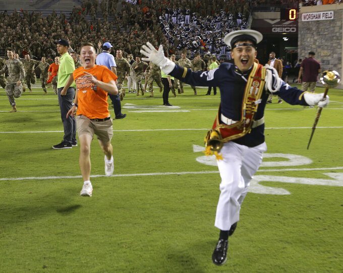Virginia Tech fans storm the field after the team's win over North Carolina in an NCAA college football game Friday, Sept. 3, 2021, in Blacksburg, Va. (Matt Gentry/The Roanoke Times via AP)
