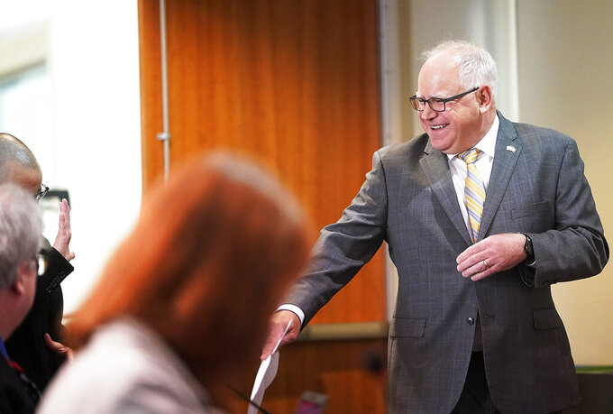 Minnesota Gov. Tim Walz is maskless but wore a big smile as he arrives for a press conference Monday, May 17, 2021, in St. Paul, Minn., to announce that he and the Legislature had agreed to spend $52 billion on the next two-year budget. (David Joles/Star Tribune via AP)