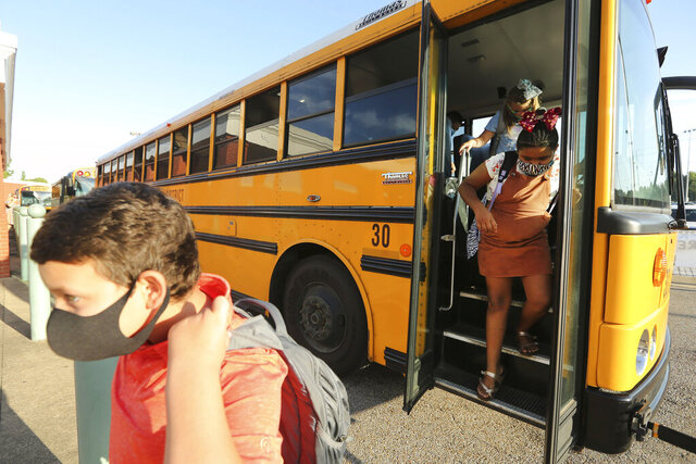 Corinth Elementary School students exit their bus wearing masks to protect against coronavirus, as they arrive for their first day back to school on Monday, July 27, 2020 in Corinth, Miss. (Adam Robison/The Northeast Mississippi Daily Journal via AP)